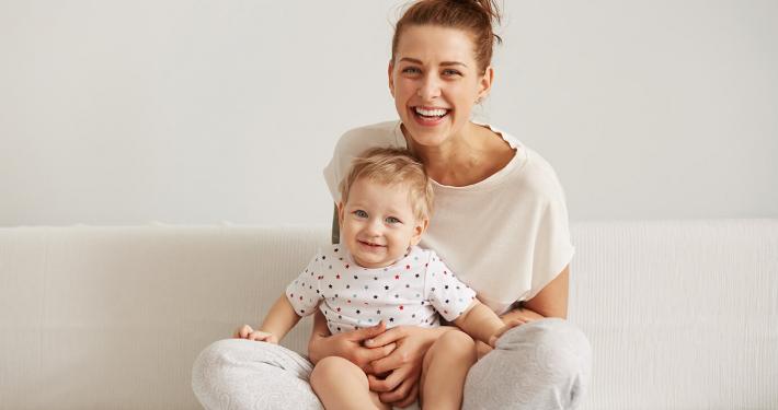 Lächende Mutter mit Kleinkind auf dem Schoß